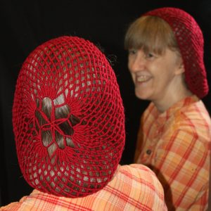 Rita is wearing a red, circular snood (hairnet).