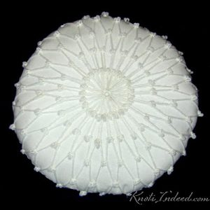 12 inch circular fiber-filled pillow covered with netting on both sides