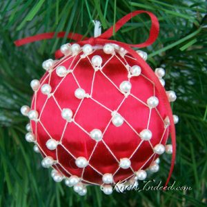 satin ornament ball enclosed in decorative netting with beads
